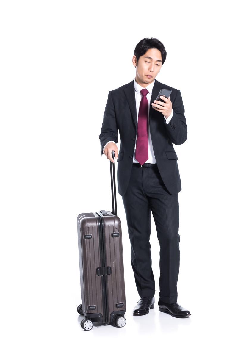 「スーツケースを持ってチェックイン時間を確認する会社員」の写真[モデル:大川竜弥]