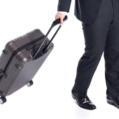 トランクをガラガラ引いて歩く会社員の写真