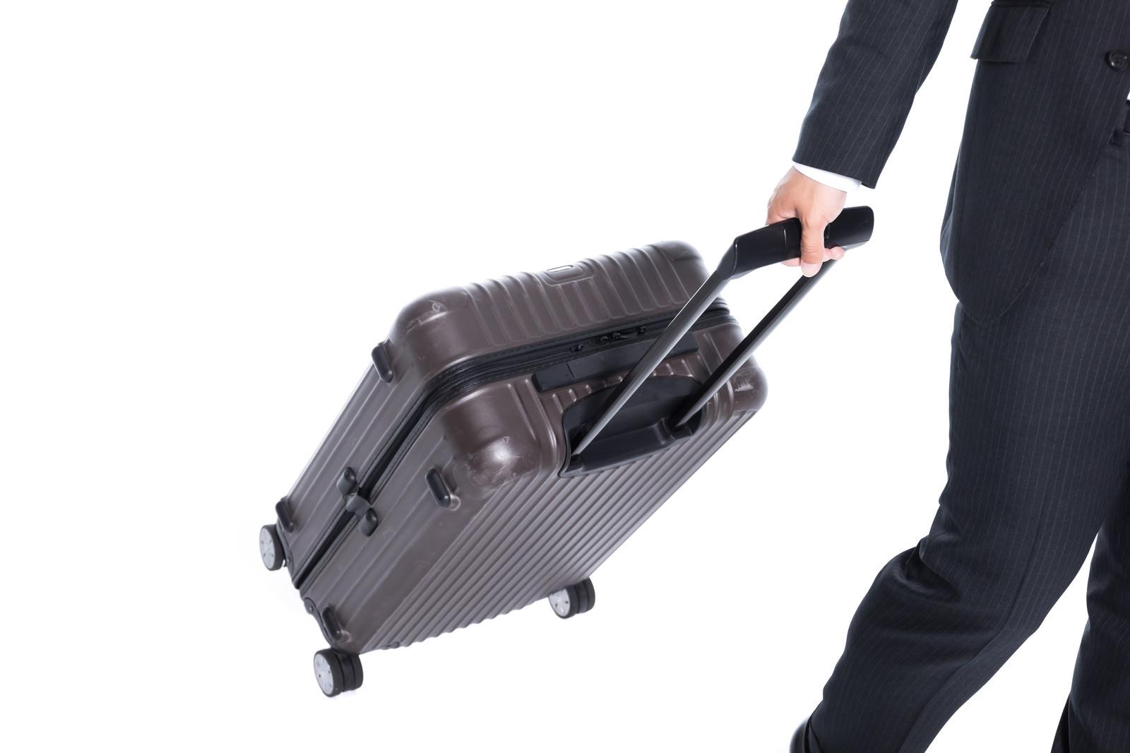 「スーツケースを引いて歩く姿(よく転倒する)」の写真[モデル:大川竜弥]
