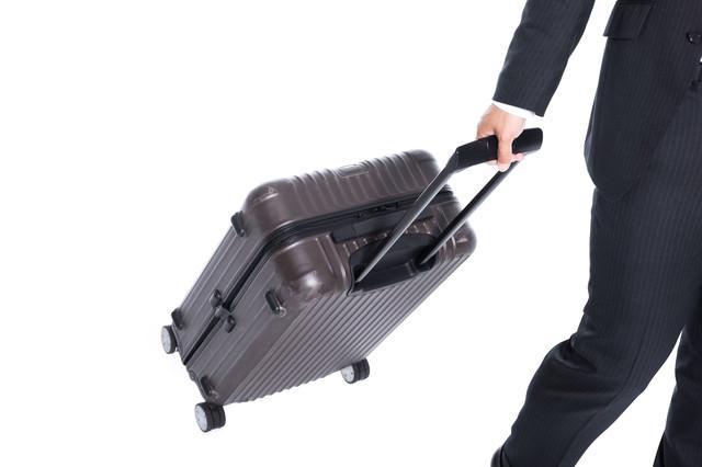 スーツケースを引いて歩く姿(よく転倒する)の写真