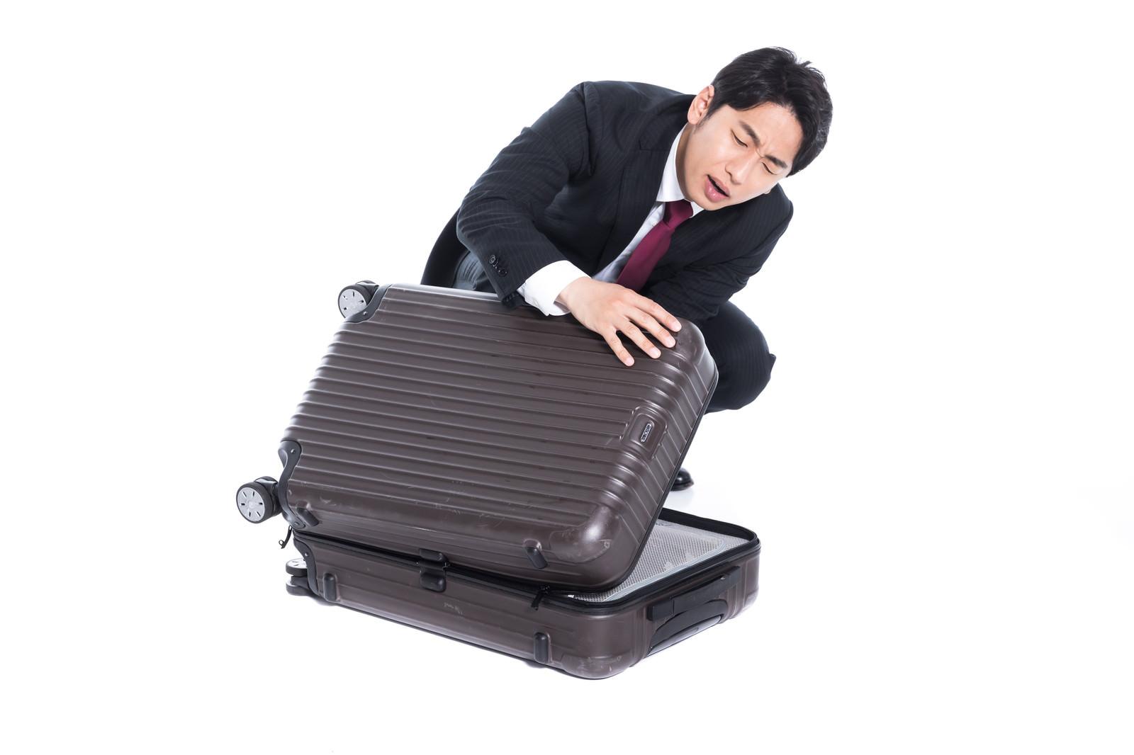 「スーツケースが閉まらない」の写真[モデル:大川竜弥]
