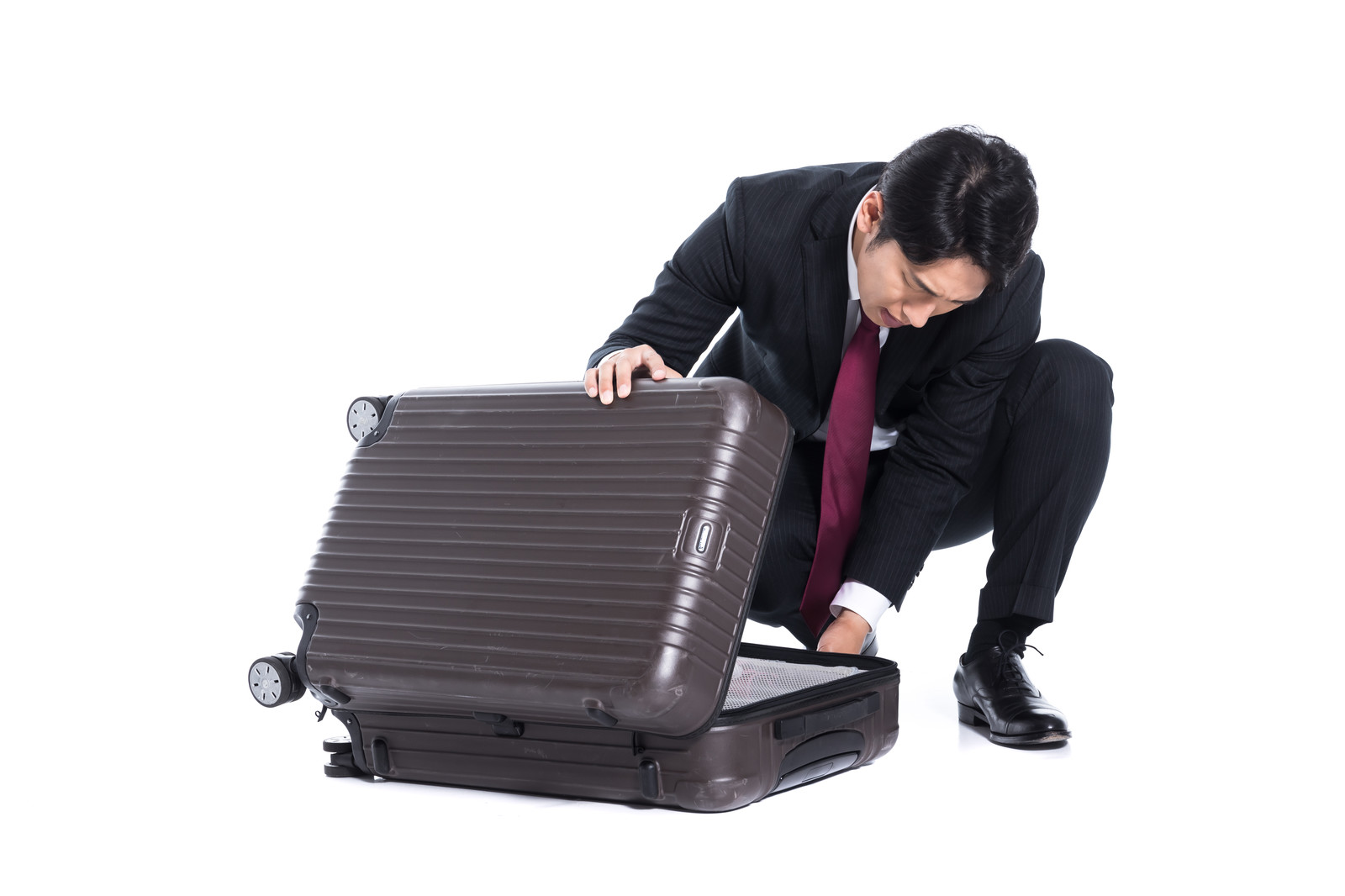 「スーツケースに荷物を詰め込むビジネスマン」の写真[モデル:大川竜弥]