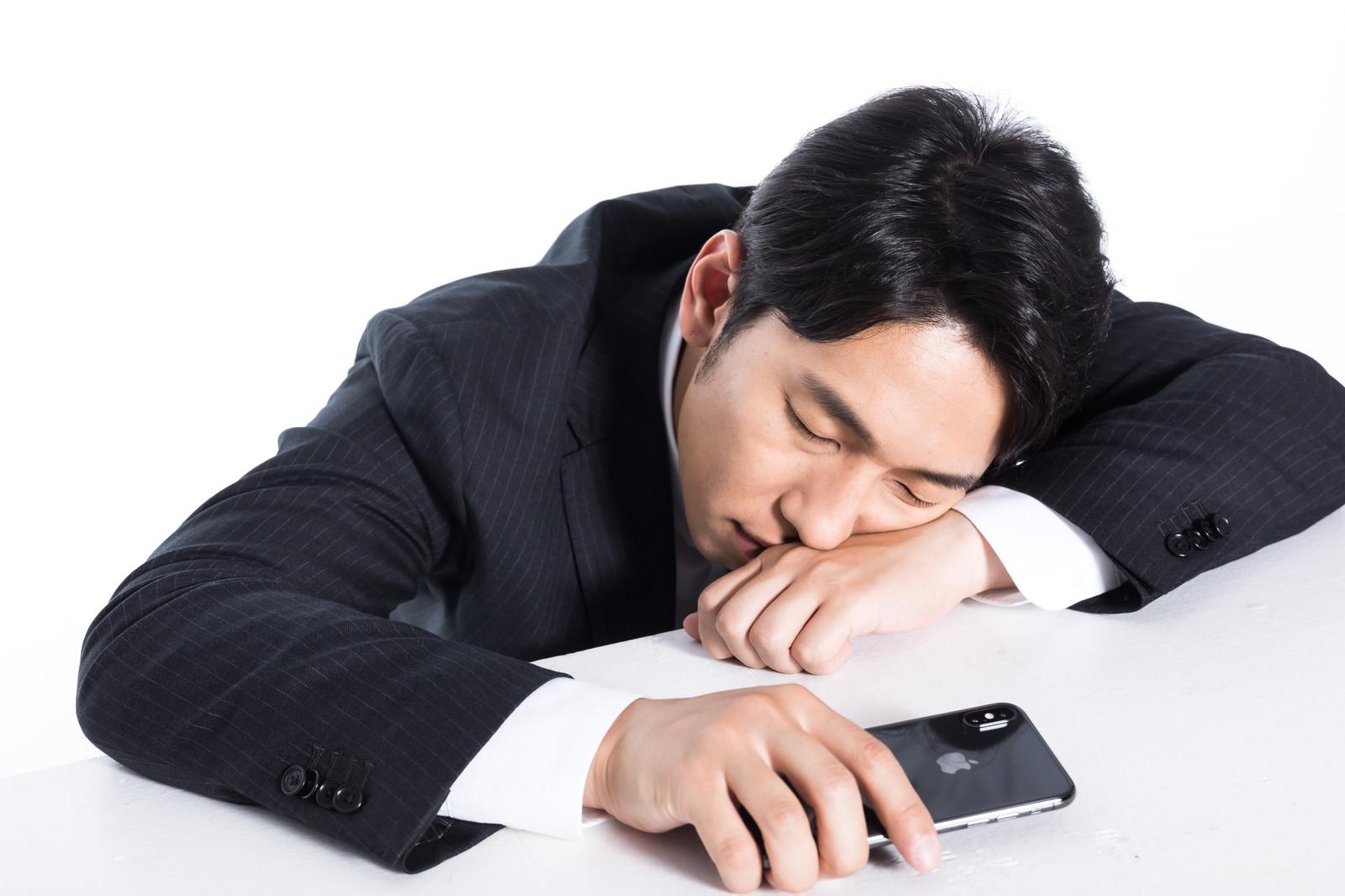 「スマホ持ちながら寝落ちする会社員」の写真[モデル:大川竜弥]