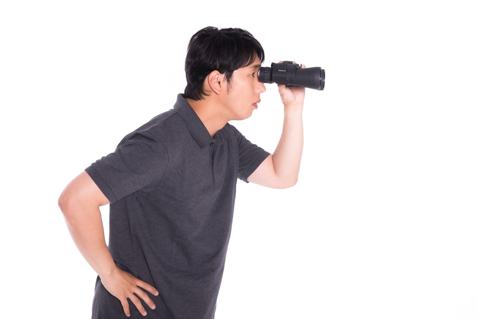 「双眼鏡を使う男性」の写真[モデル:大川竜弥]