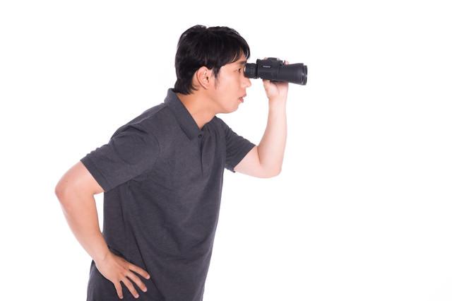 双眼鏡を使う男性の写真