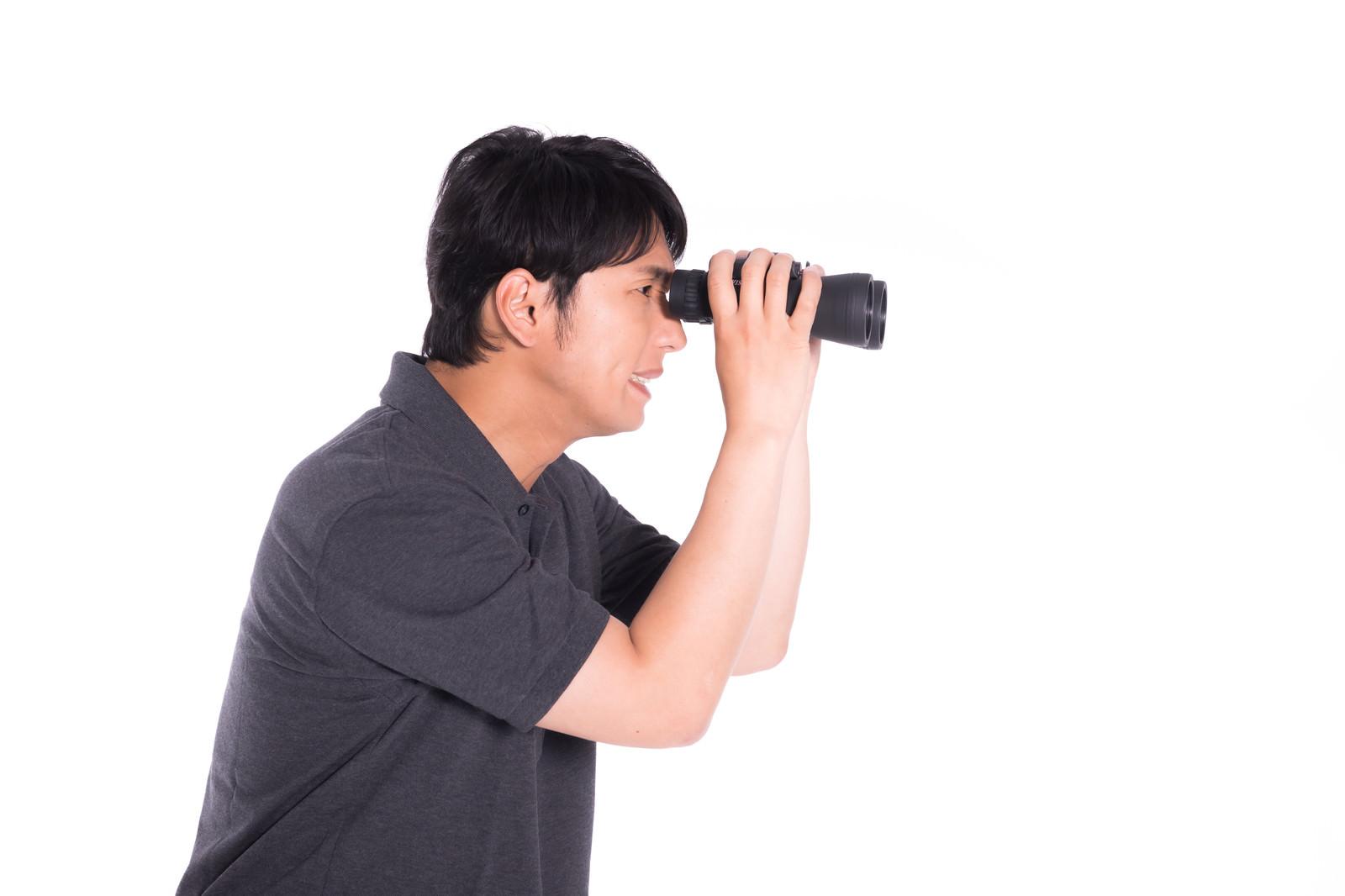 「遠すぎて双眼鏡でもなかなか見えづらい」の写真[モデル:大川竜弥]