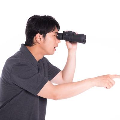 双眼鏡を覗きながら観戦する男性の写真