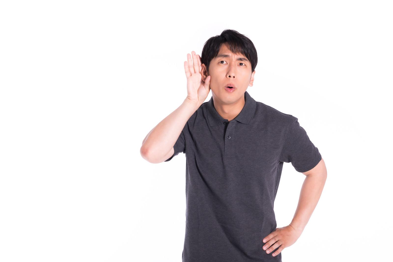 「内緒話に耳を傾ける男性」の写真[モデル:大川竜弥]