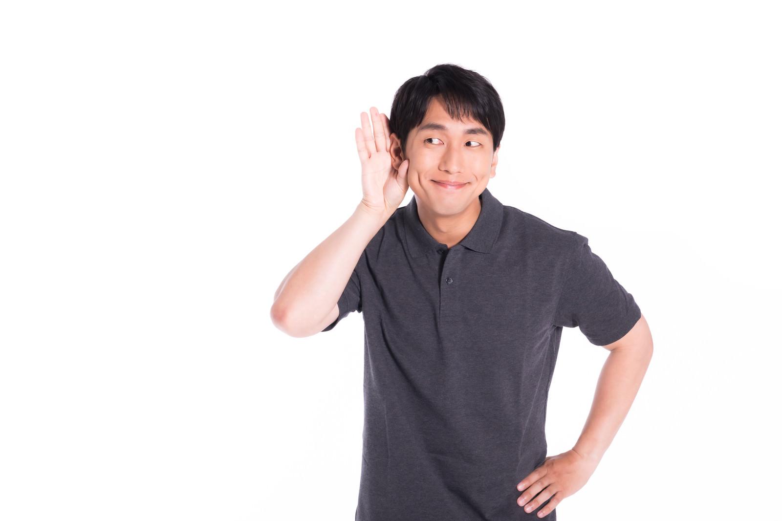 「自分の良い噂ににんまりする男性」の写真[モデル:大川竜弥]