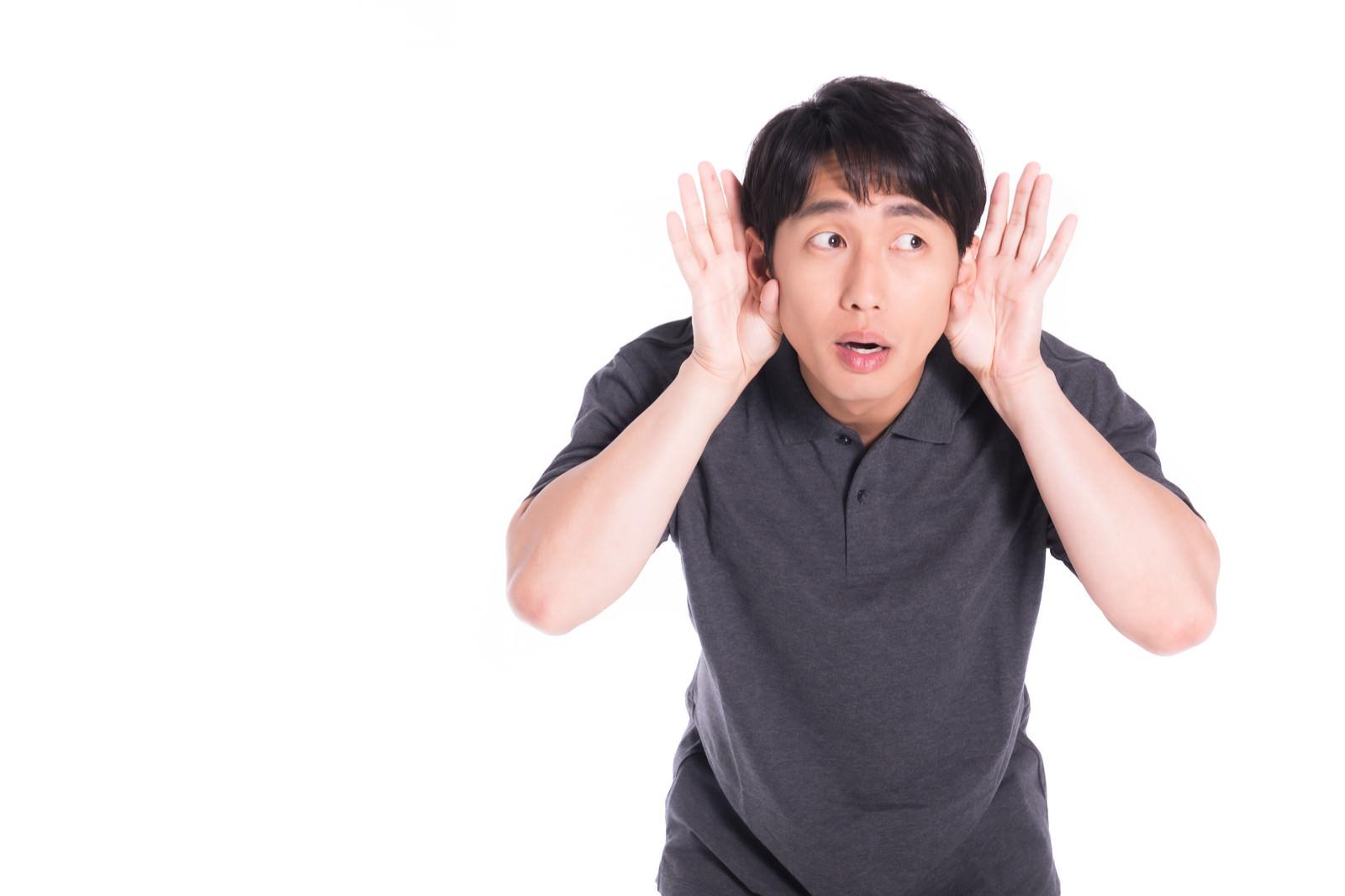 「耳をそばだてる男性」の写真[モデル:大川竜弥]