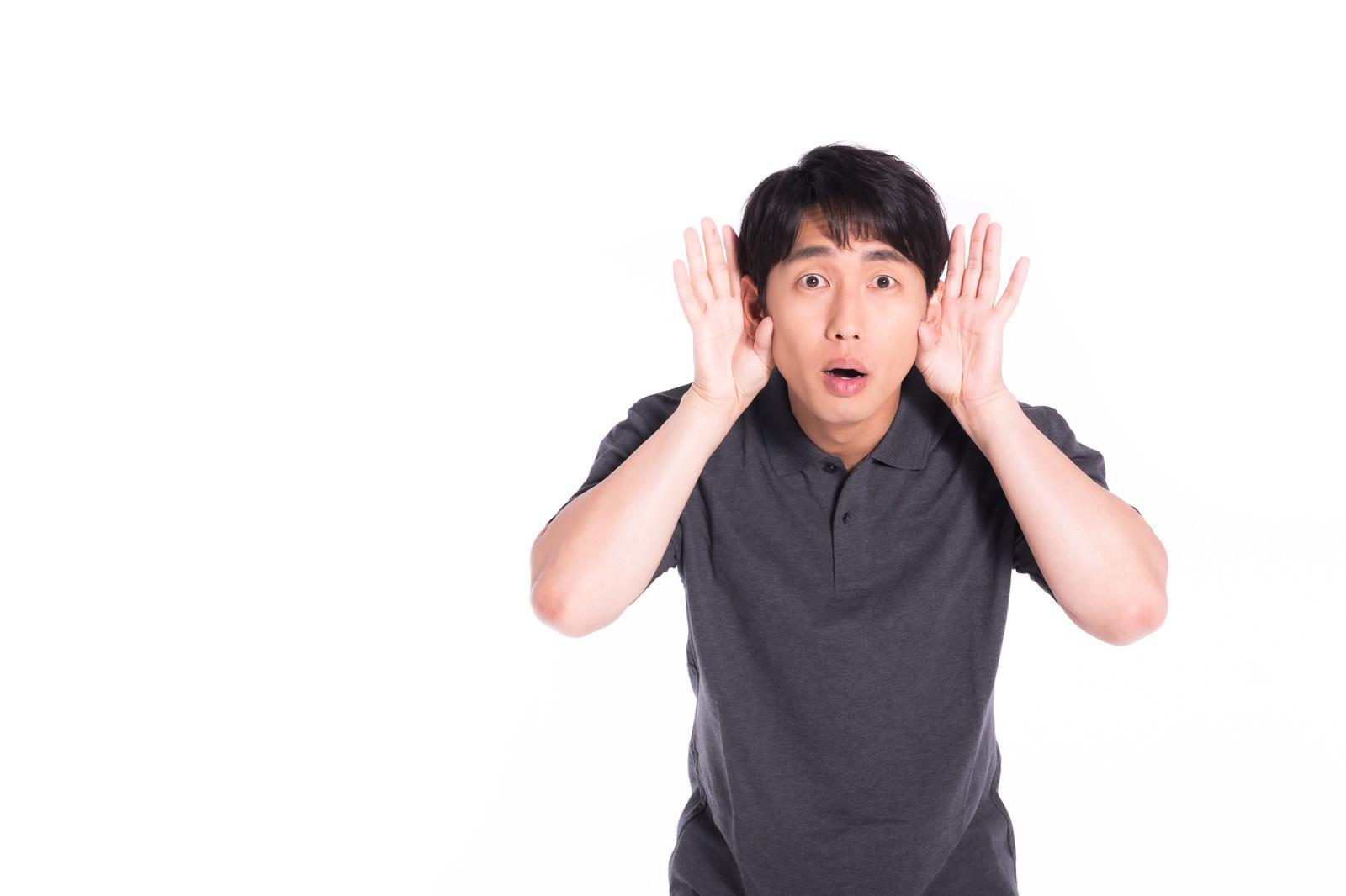 「聞き耳を立てる男性」の写真[モデル:大川竜弥]
