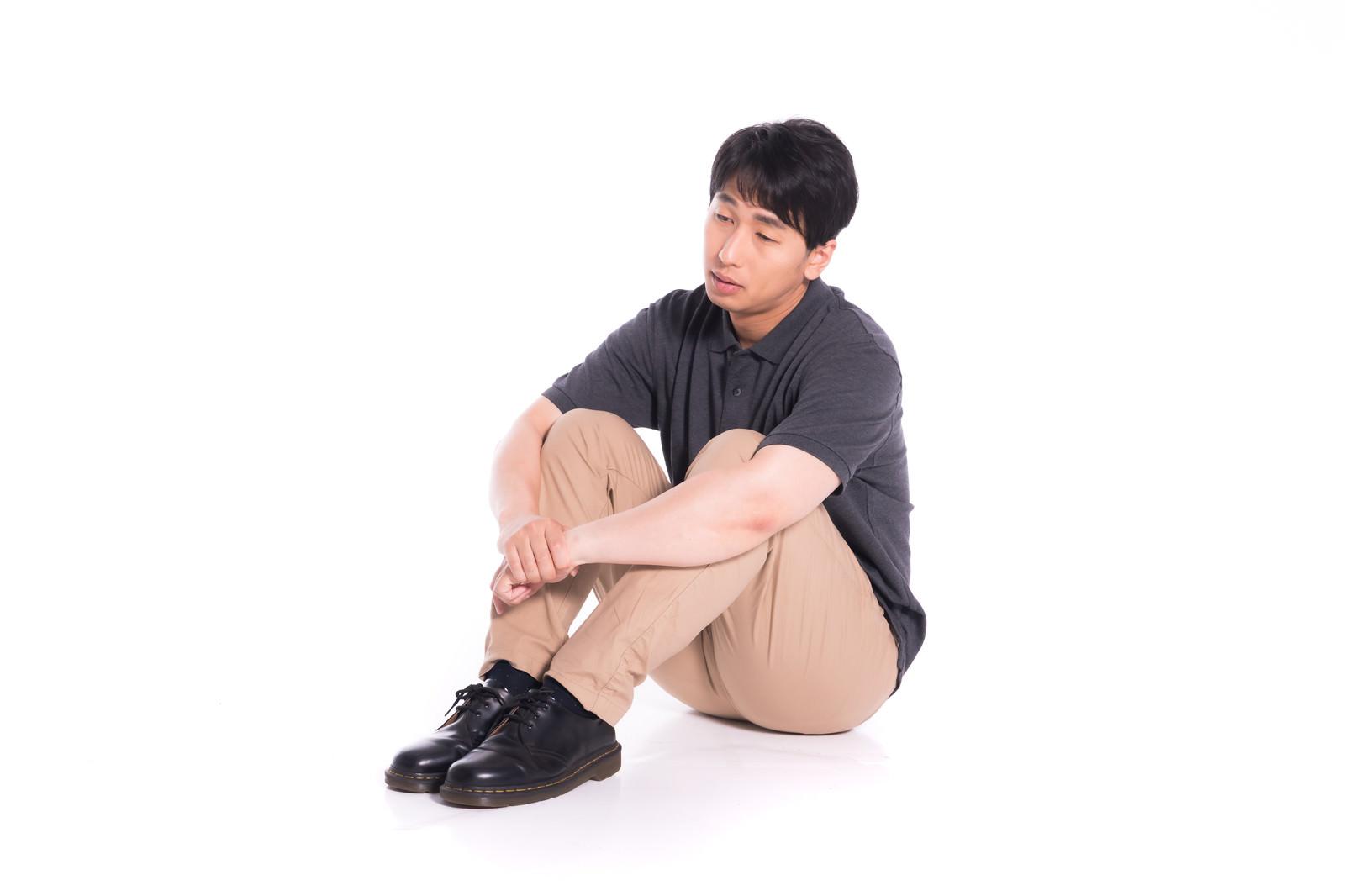 「体育座りで途方に暮れる男性」の写真[モデル:大川竜弥]