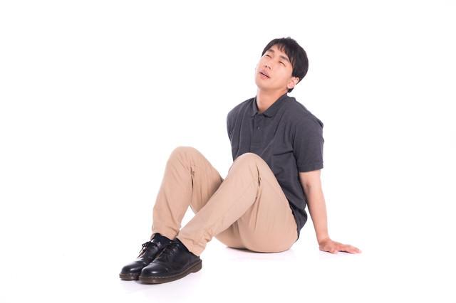 疲れて座り込む男性の写真