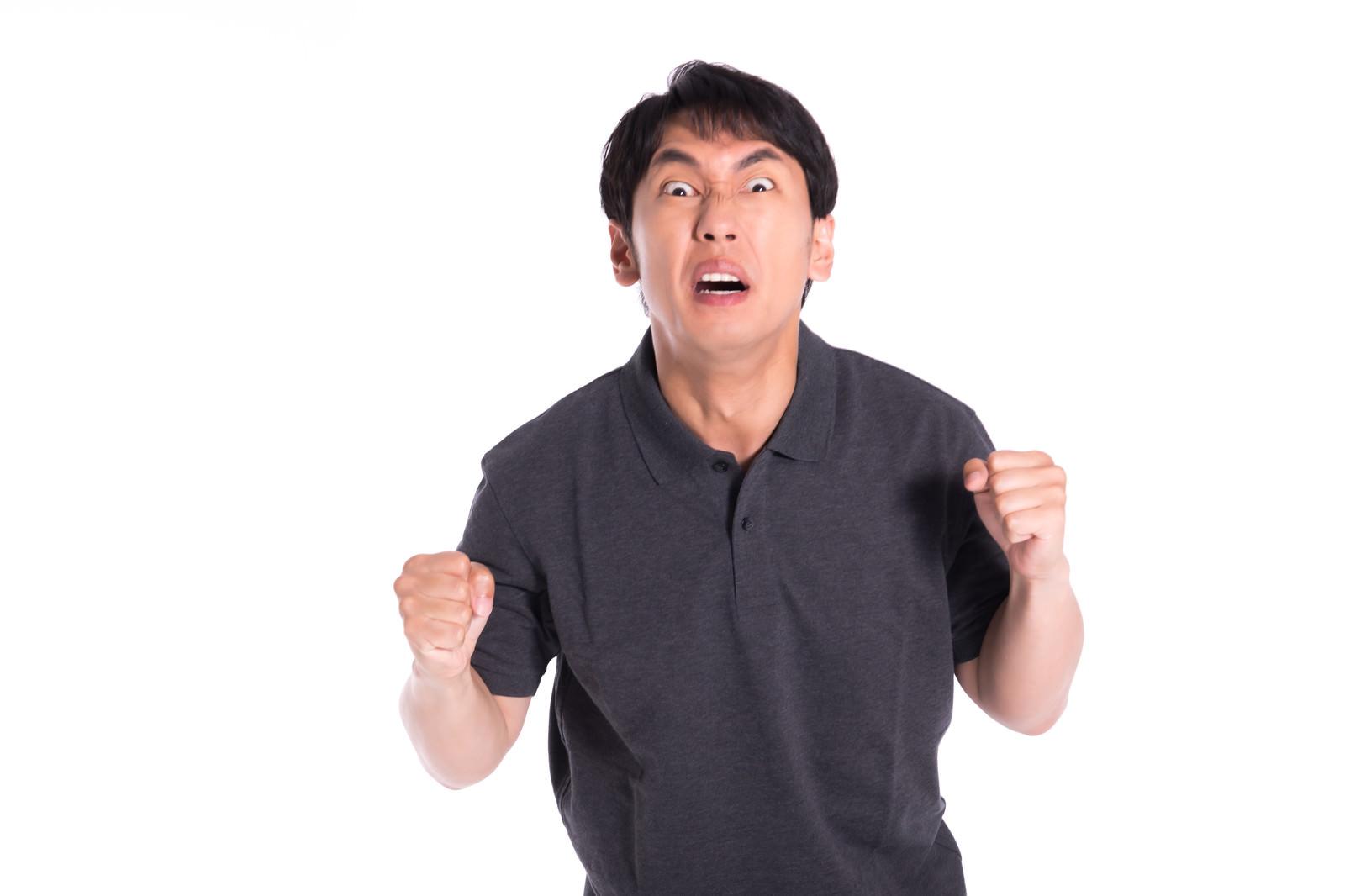 「目をむいて怒る男性」の写真[モデル:大川竜弥]