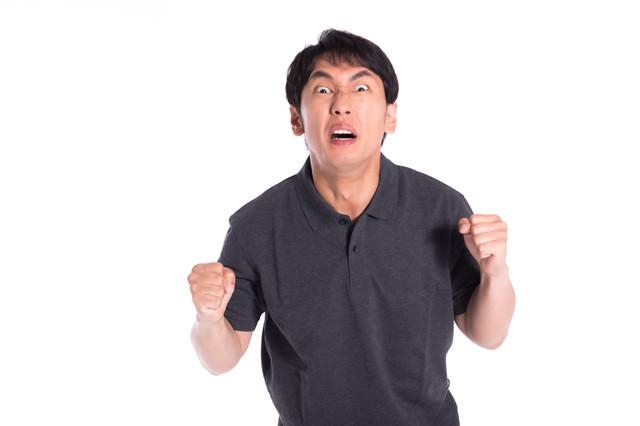 目をむいて怒る男性の写真