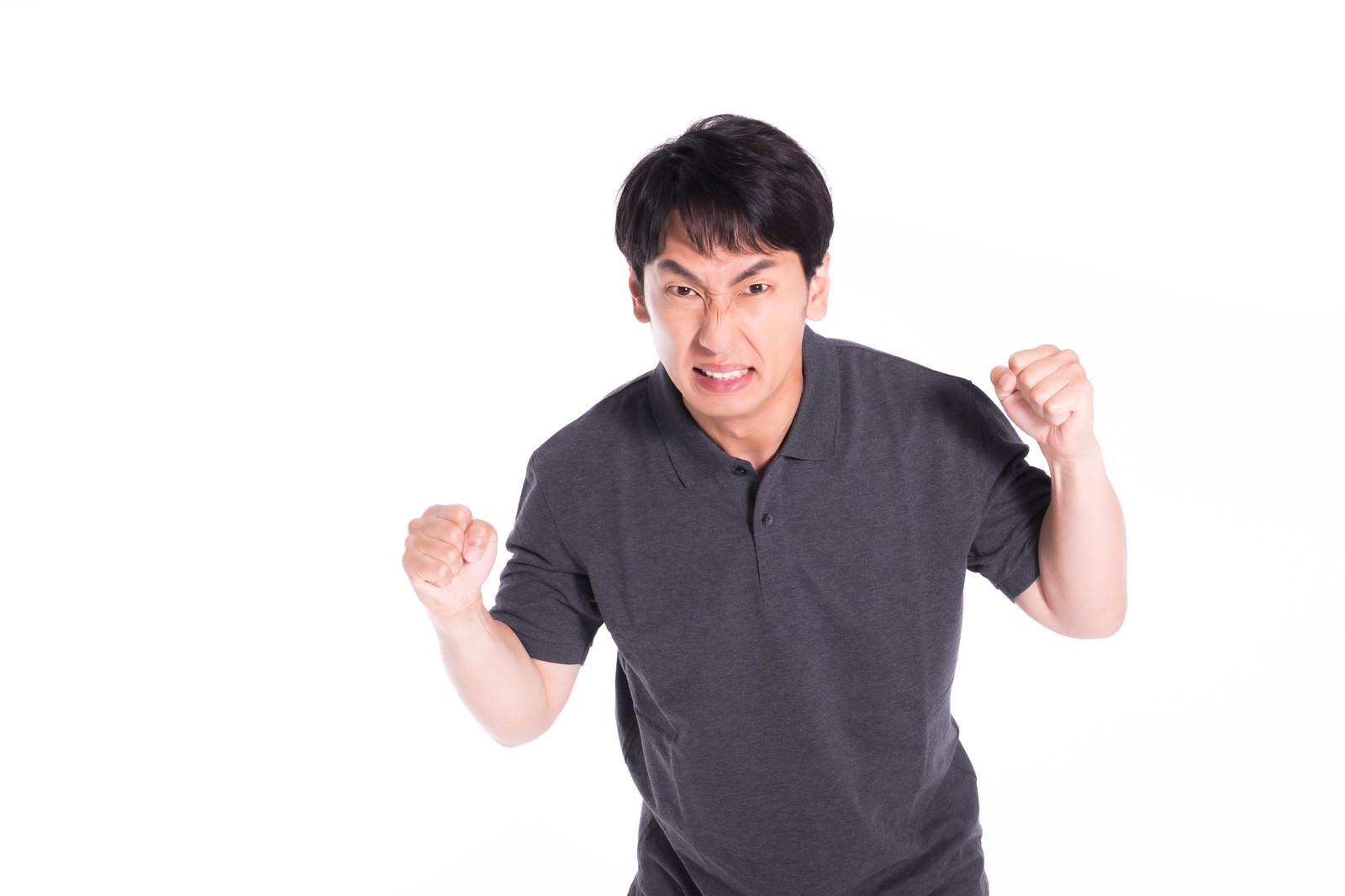 「怒りに任せて暴力をふるいそうになるも我慢する男性」の写真[モデル:大川竜弥]