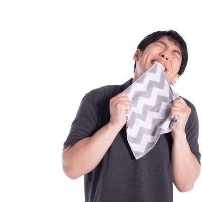 恋人からもらったハンカチを嬉しそうに噛む男性の写真