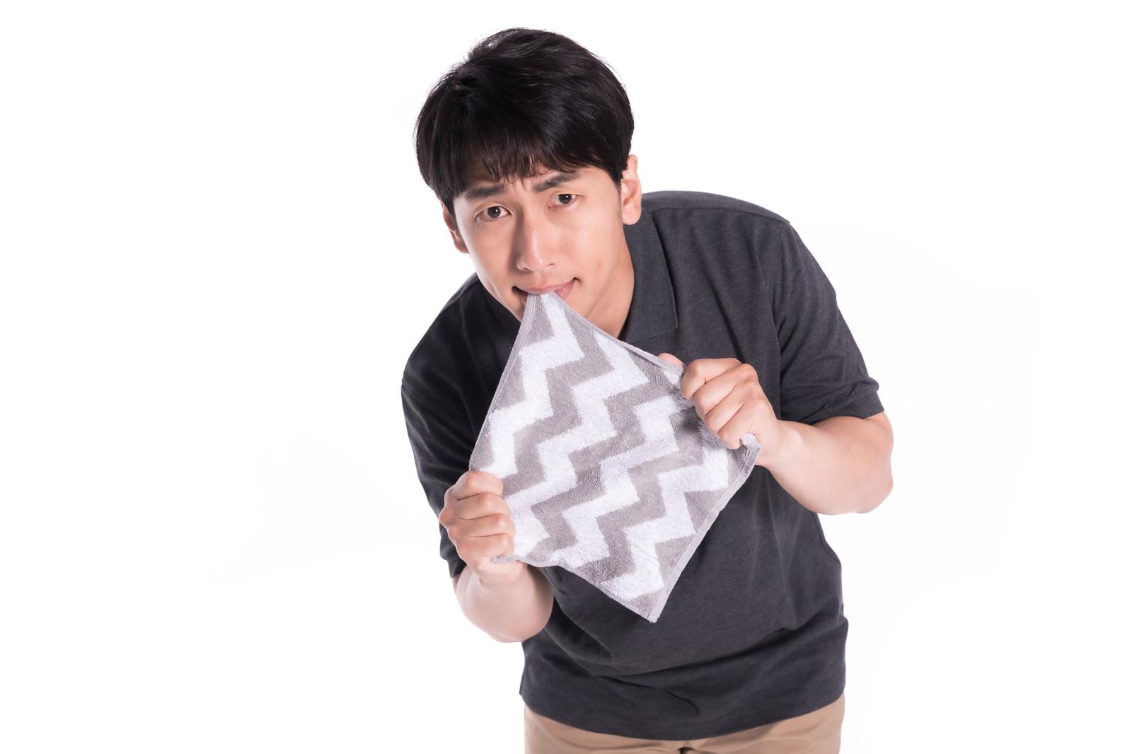 「口と手でハンカチを引っ張る男性」の写真[モデル:大川竜弥]
