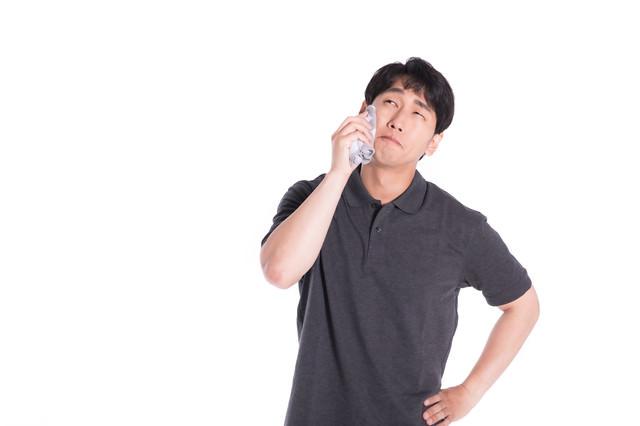 夏日で汗を拭く男性の写真