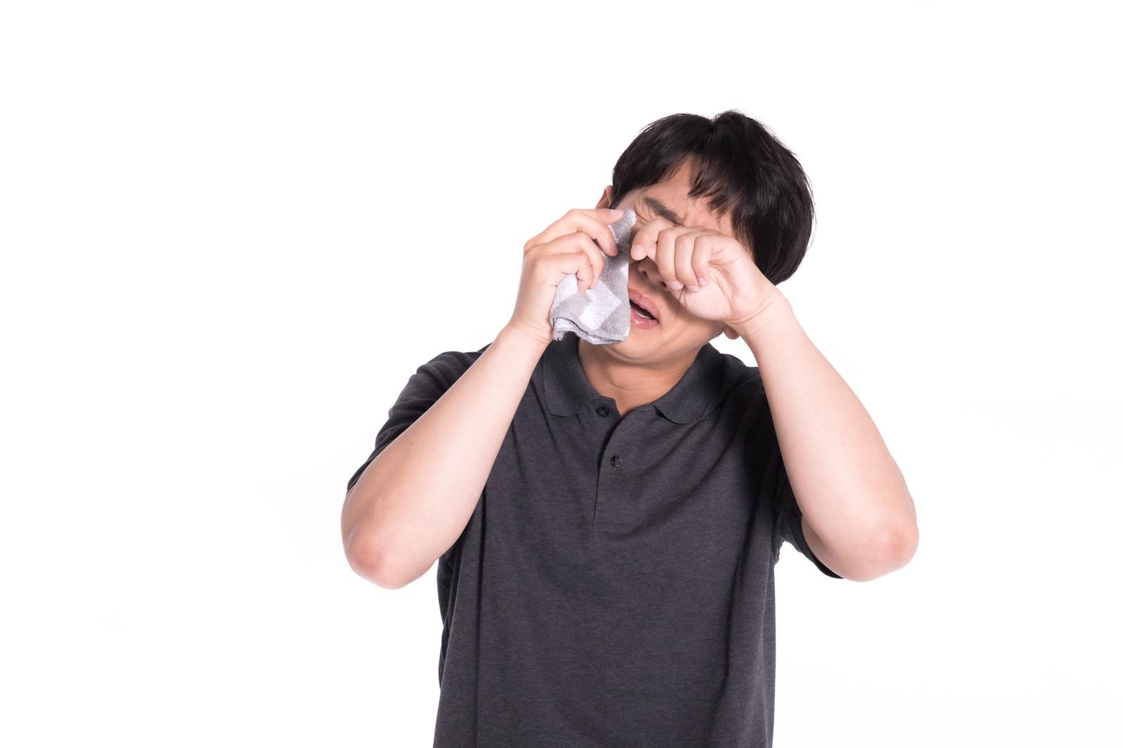 「泣きながらハンカチで涙を拭う男性」の写真[モデル:大川竜弥]