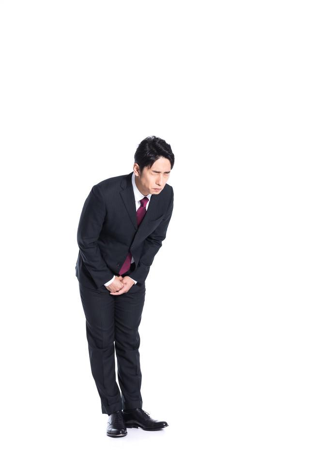 涙をこらえて謝罪をするスーツ姿の男性の写真