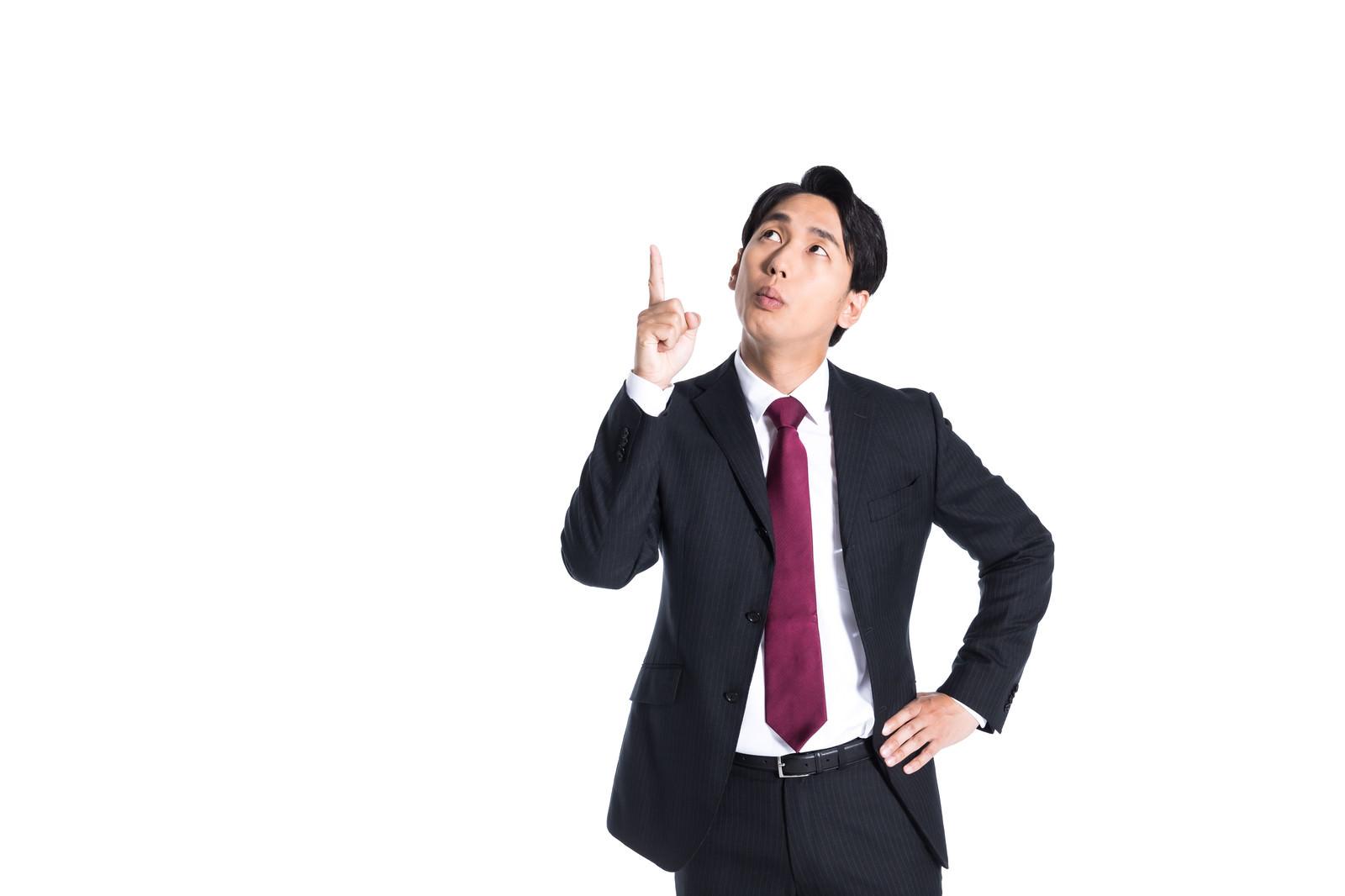 「上方向を指さすスーツ姿の男性」の写真[モデル:大川竜弥]