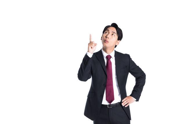 上方向を指さすスーツ姿の男性の写真
