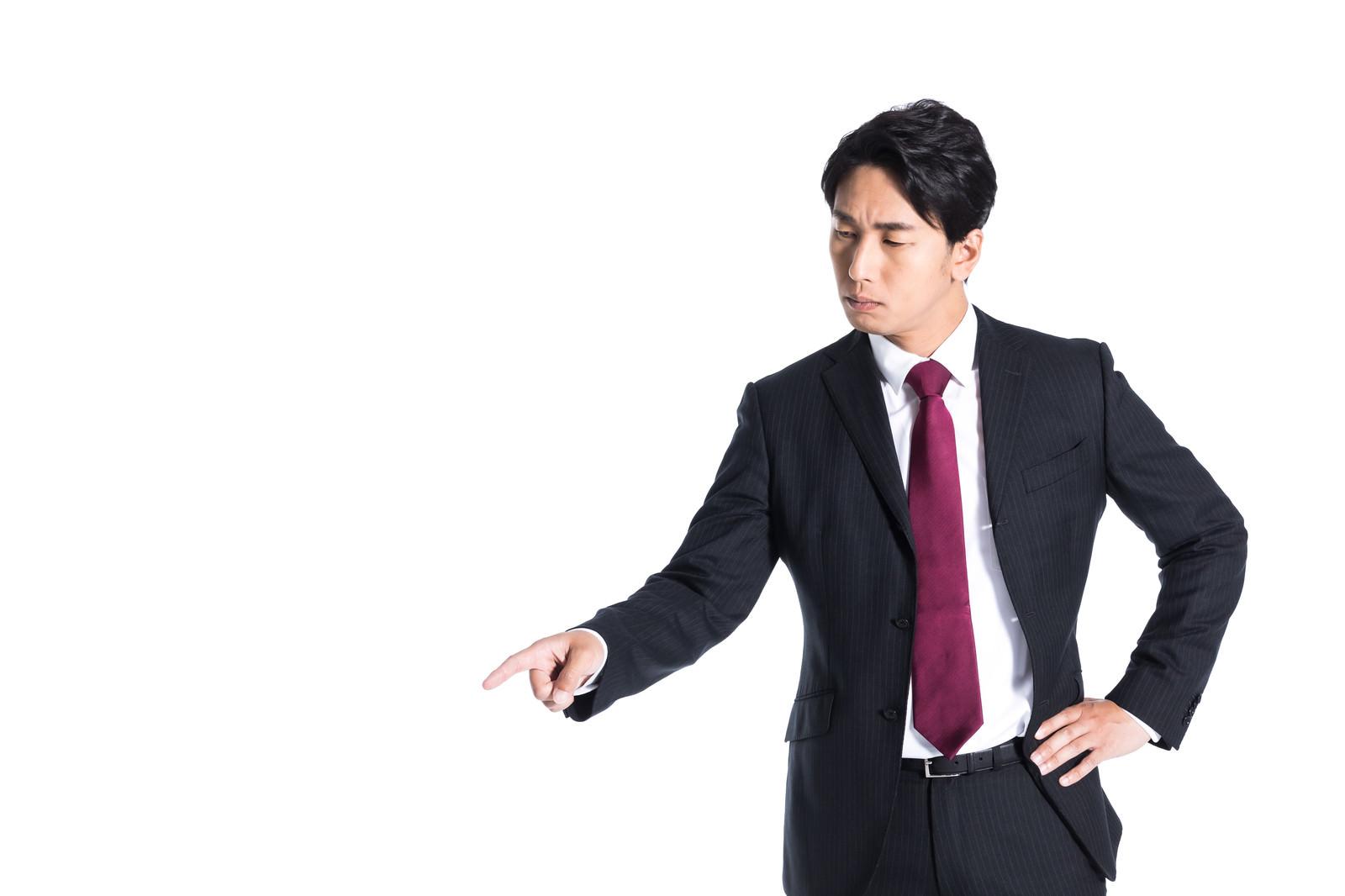 「左下を指さすスーツ姿の会社員」の写真[モデル:大川竜弥]