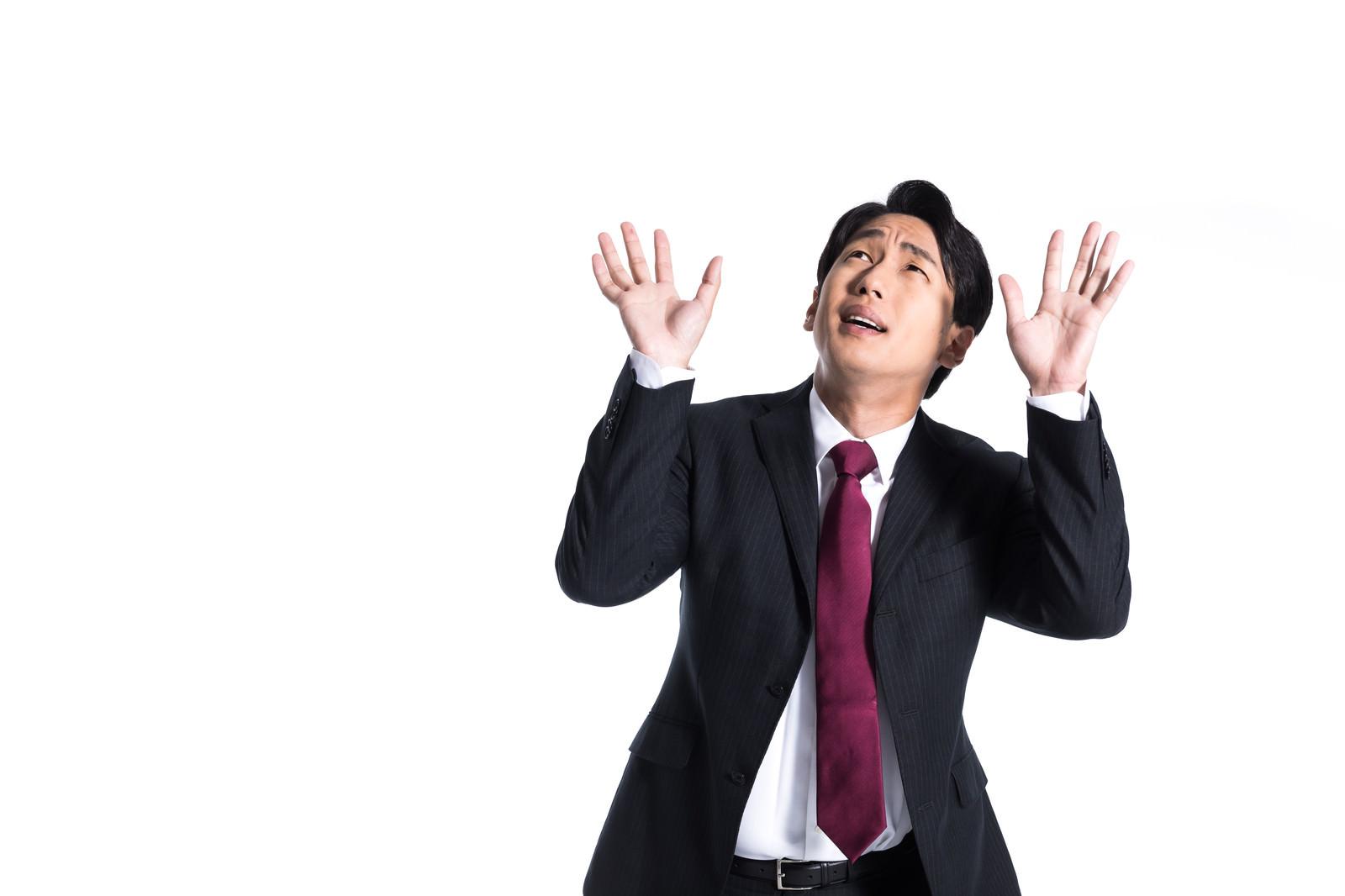 「仕事のプレッシャーに押しつぶされそうな会社員」の写真[モデル:大川竜弥]