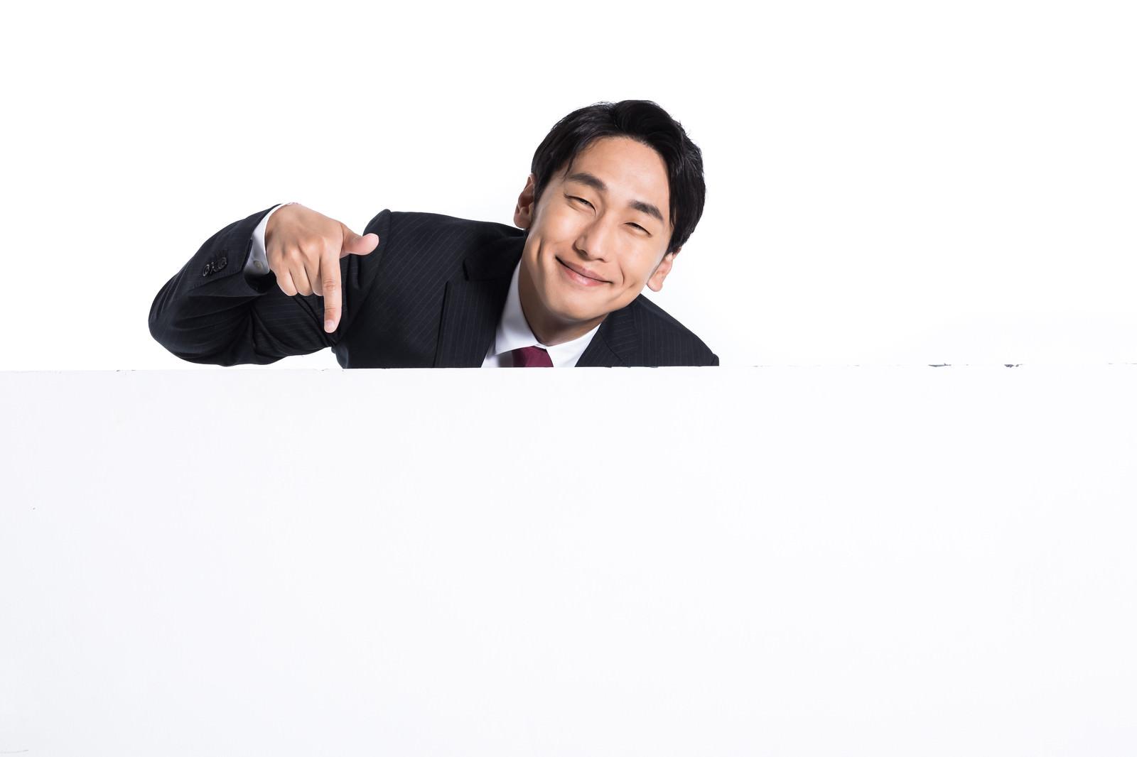「満面の笑みで下を指さす会社員」の写真[モデル:大川竜弥]