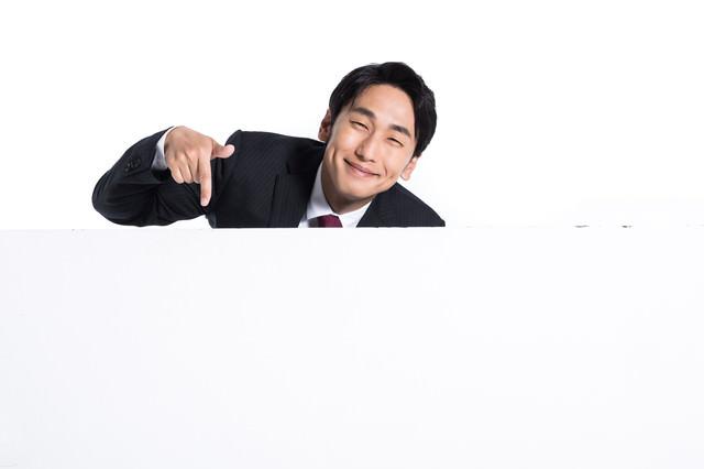 満面の笑みで下を指さす会社員の写真