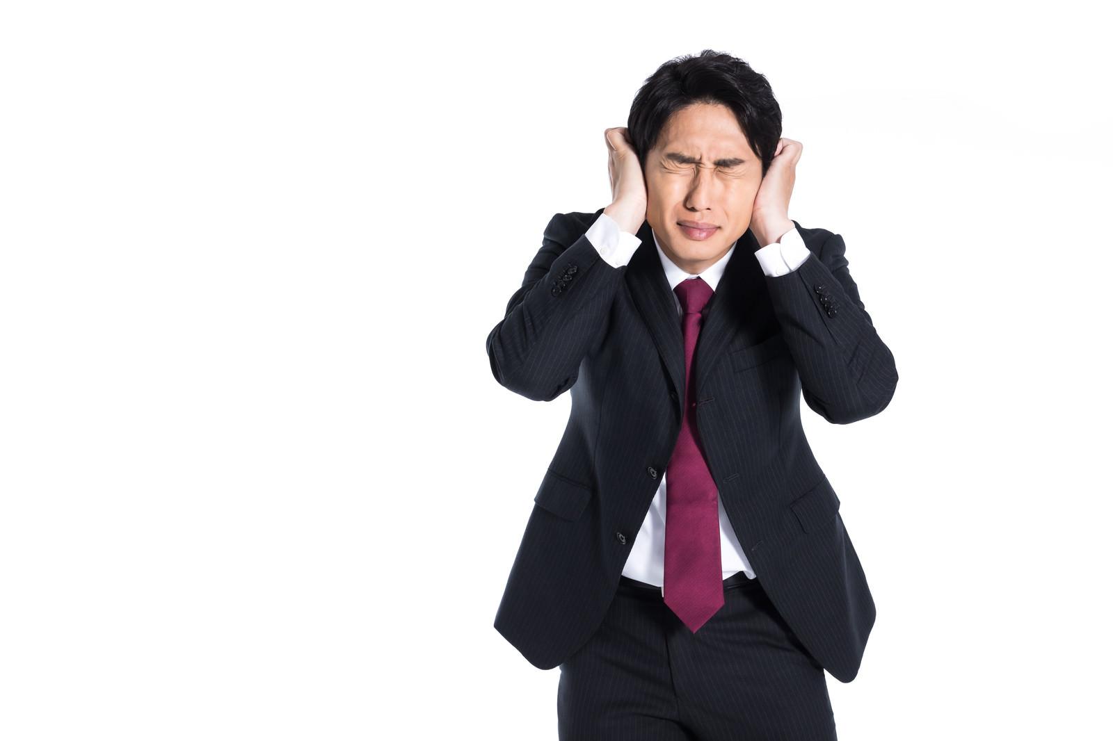 「大量のクレームに耳を塞ぐ男性」の写真[モデル:大川竜弥]