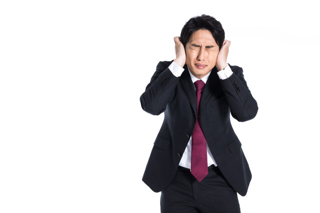大量のクレームに耳を塞ぐ男性の写真