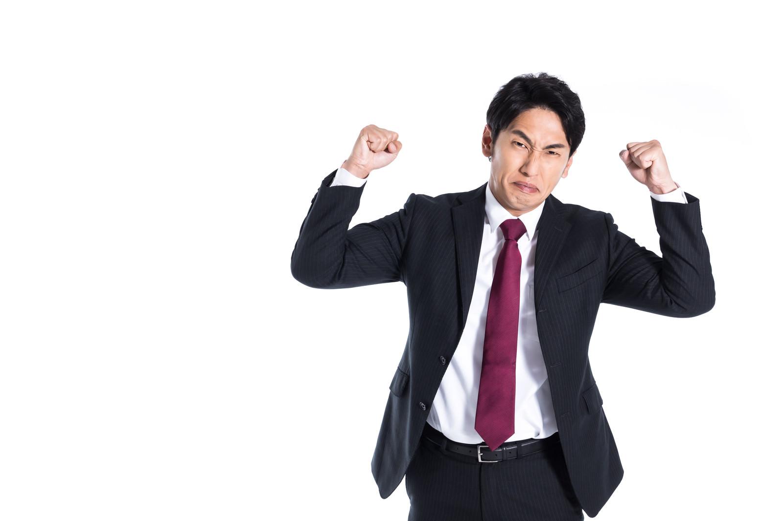 「強面で拳を振り上げて悔しがる会社員」の写真[モデル:大川竜弥]