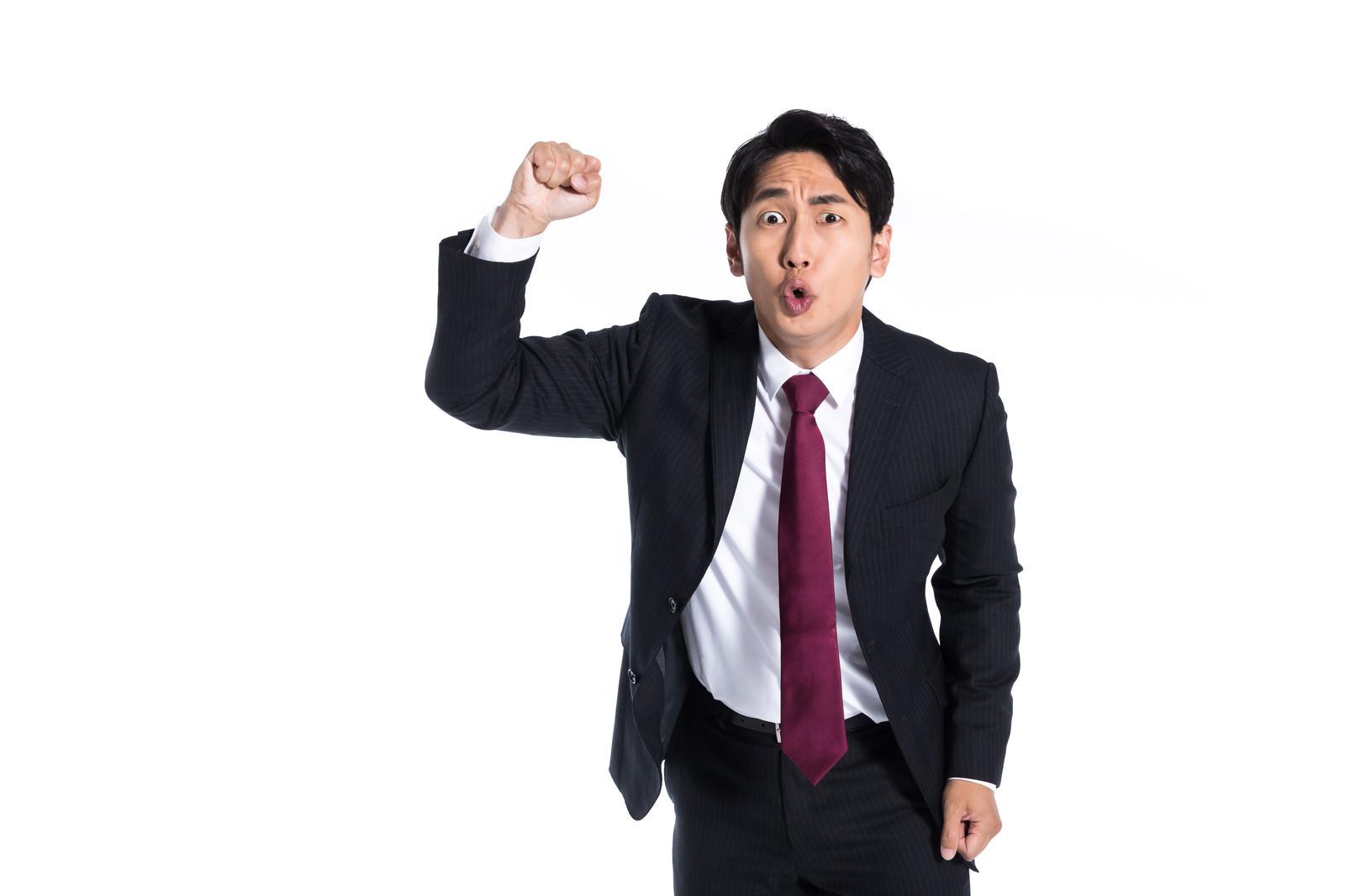 「拳を振り上げて憤怒する会社員」の写真[モデル:大川竜弥]