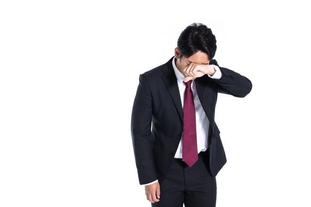 悔し泣きする営業マンの写真