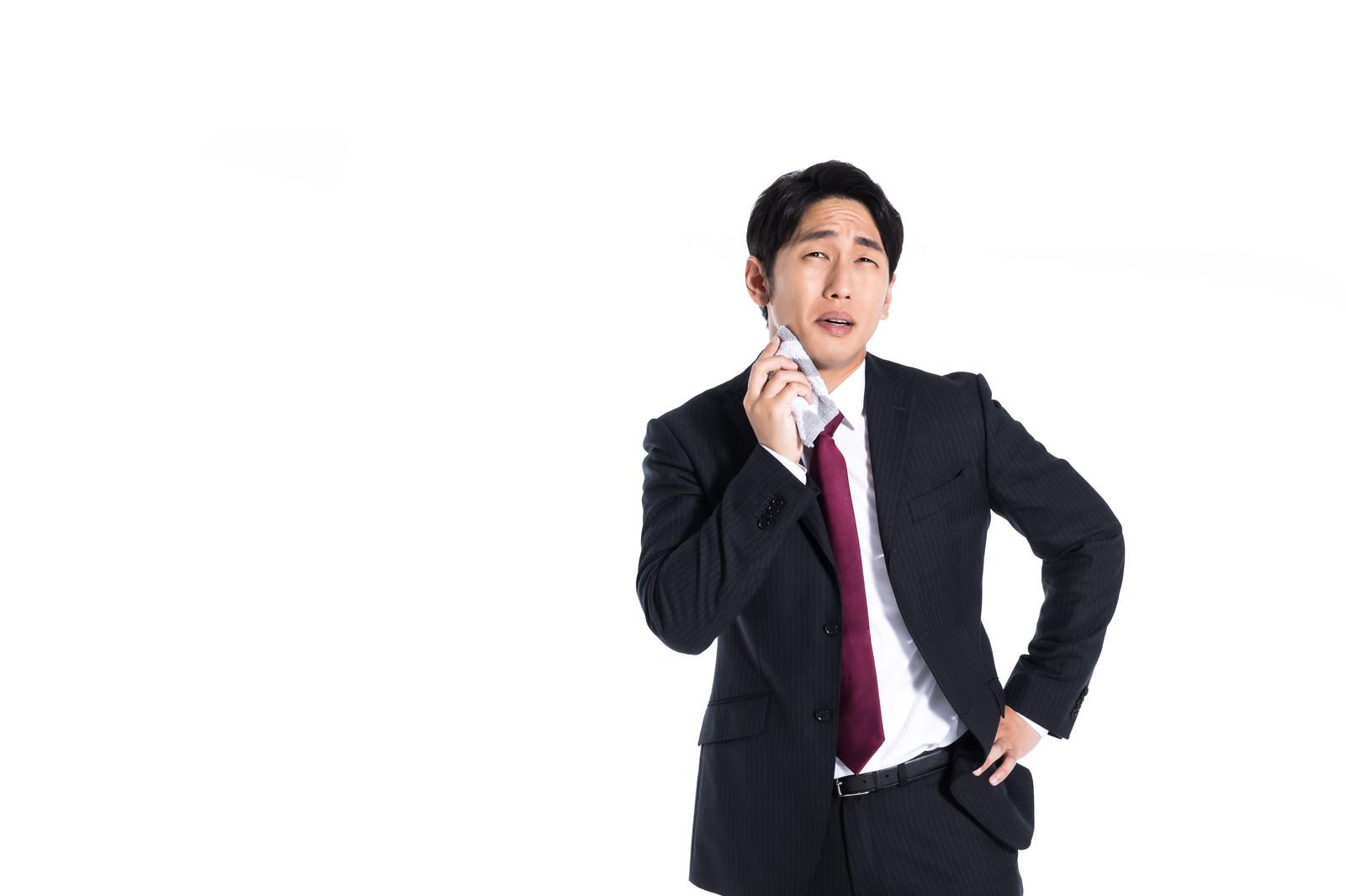 「ハンカチで汗を拭きながら営業するサラリーマン」の写真[モデル:大川竜弥]