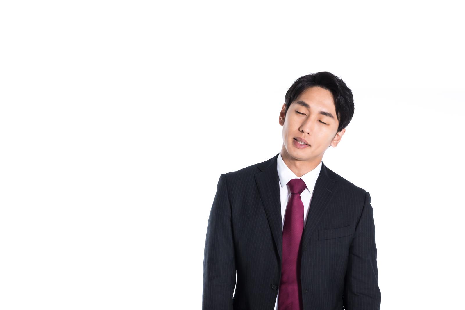 「立ちながら寝落ち寸前の営業マン」の写真[モデル:大川竜弥]