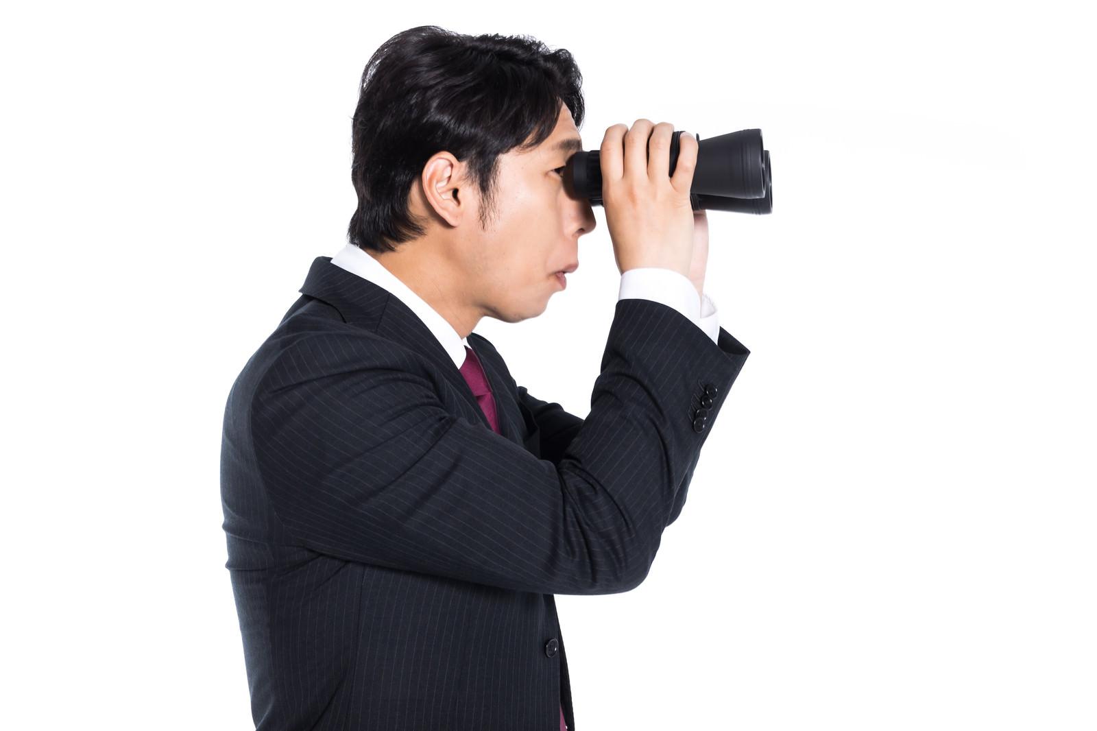「双眼鏡で競合他社をリサーチするエージェント」の写真[モデル:大川竜弥]
