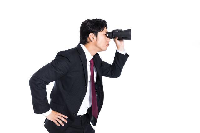 双眼鏡を覗く会社員の写真