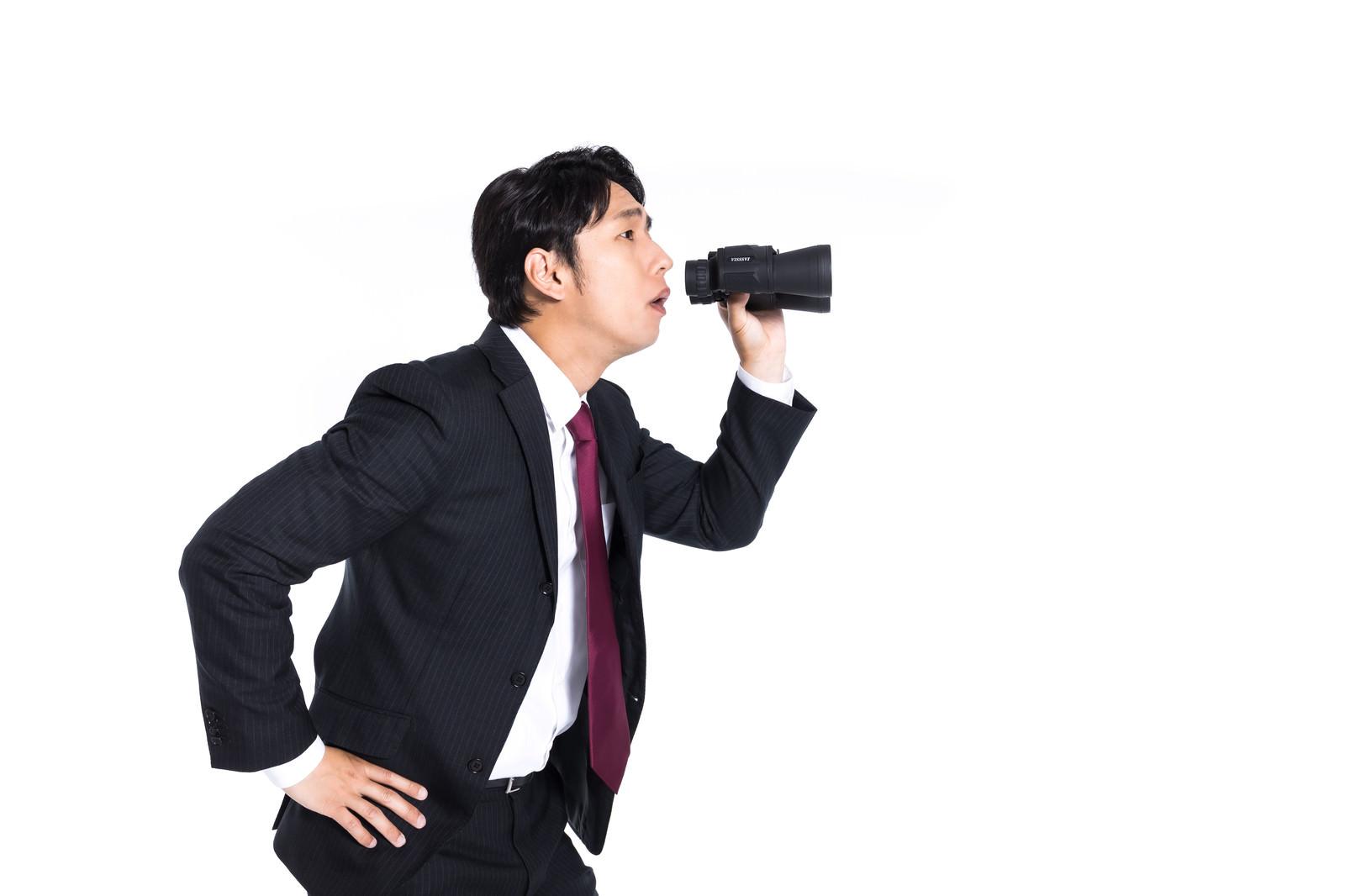 「双眼鏡を持ってサボっている従業員を監視するリーダー」の写真[モデル:大川竜弥]