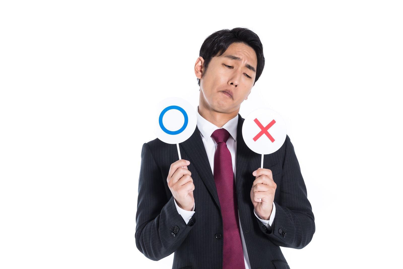 「○×どちらにするか検討する会社員」の写真[モデル:大川竜弥]