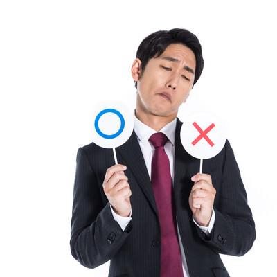 ○×どちらにするか検討する会社員の写真