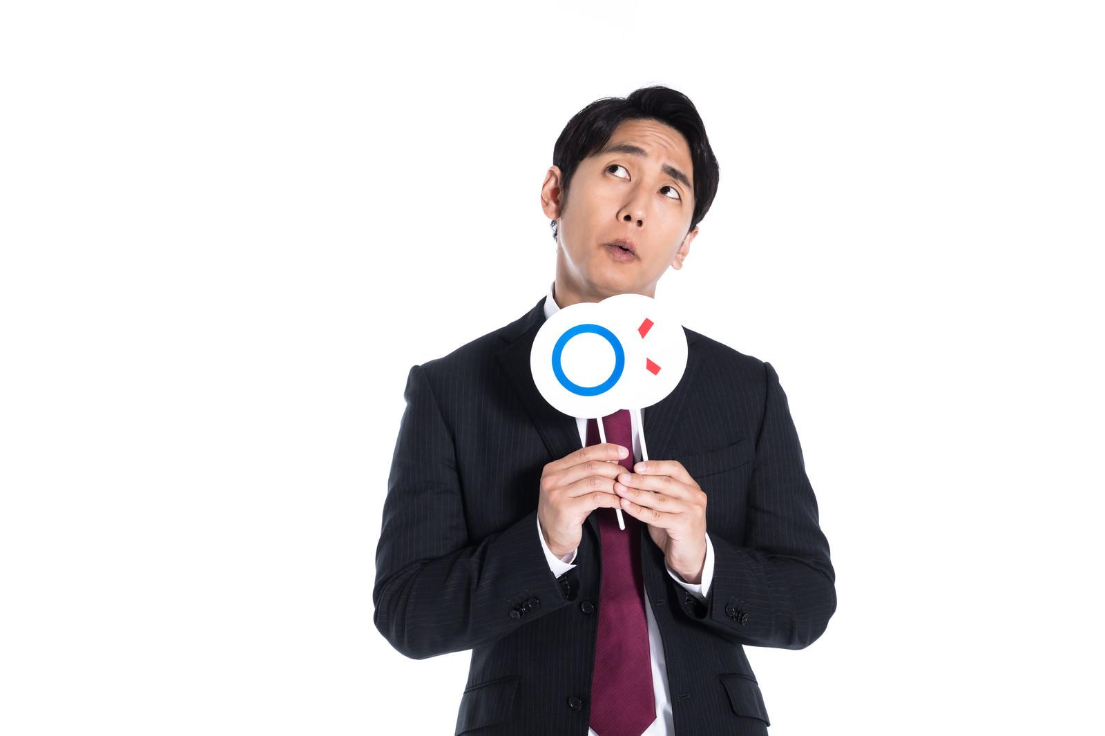 「○×クイズを考える男性」の写真[モデル:大川竜弥]