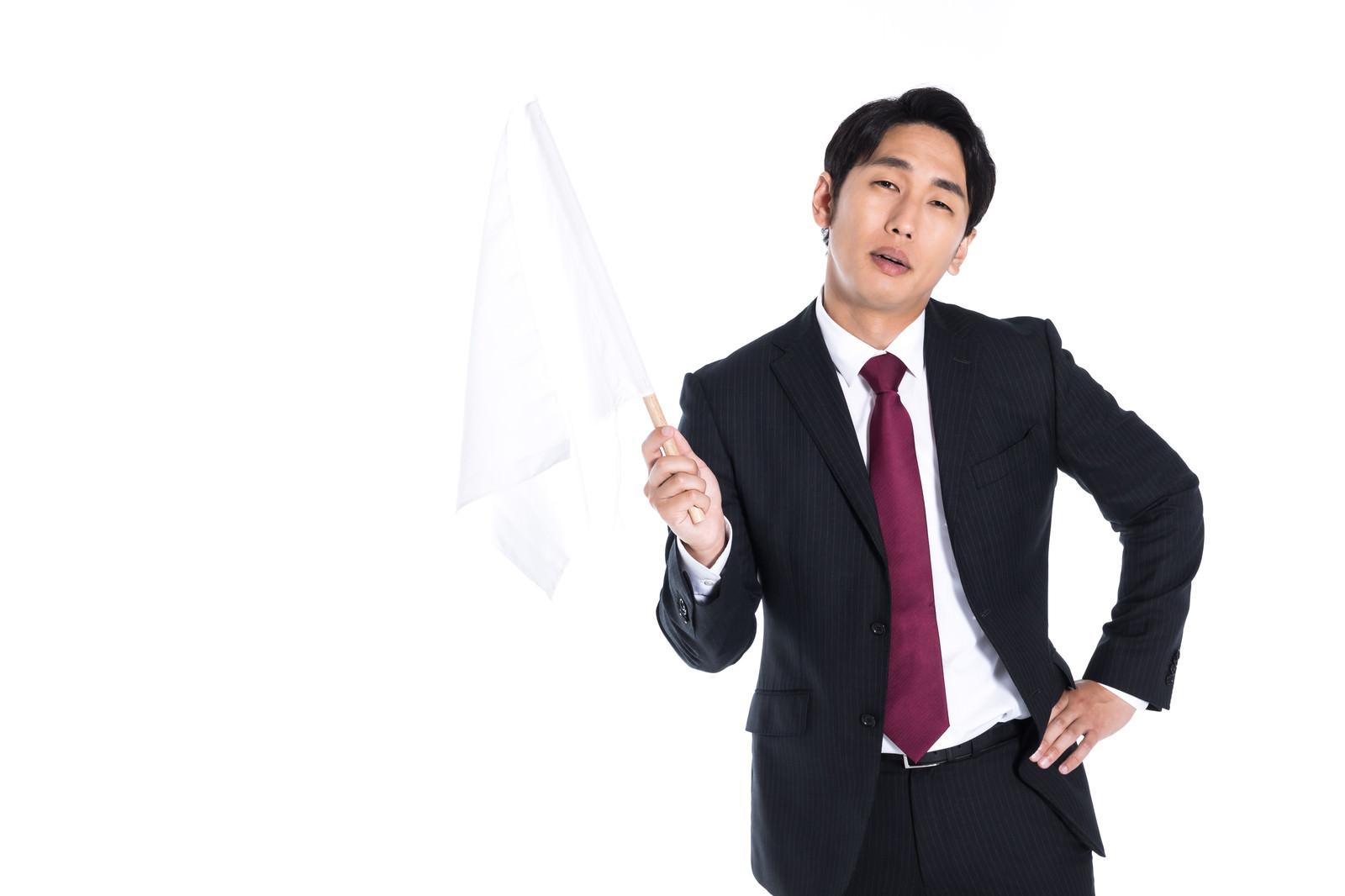 「嫌々白旗を揚げる会社員」の写真[モデル:大川竜弥]