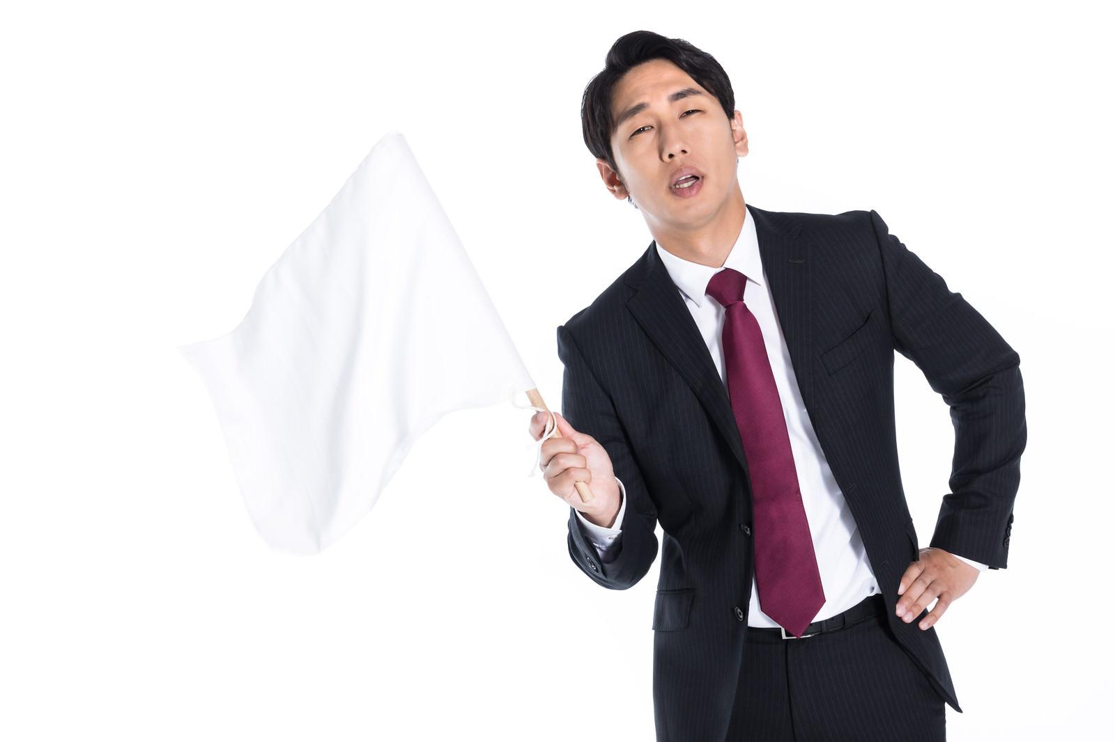 「白旗を振って負けを認める会社員」の写真[モデル:大川竜弥]