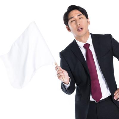 白旗を振って負けを認める会社員の写真