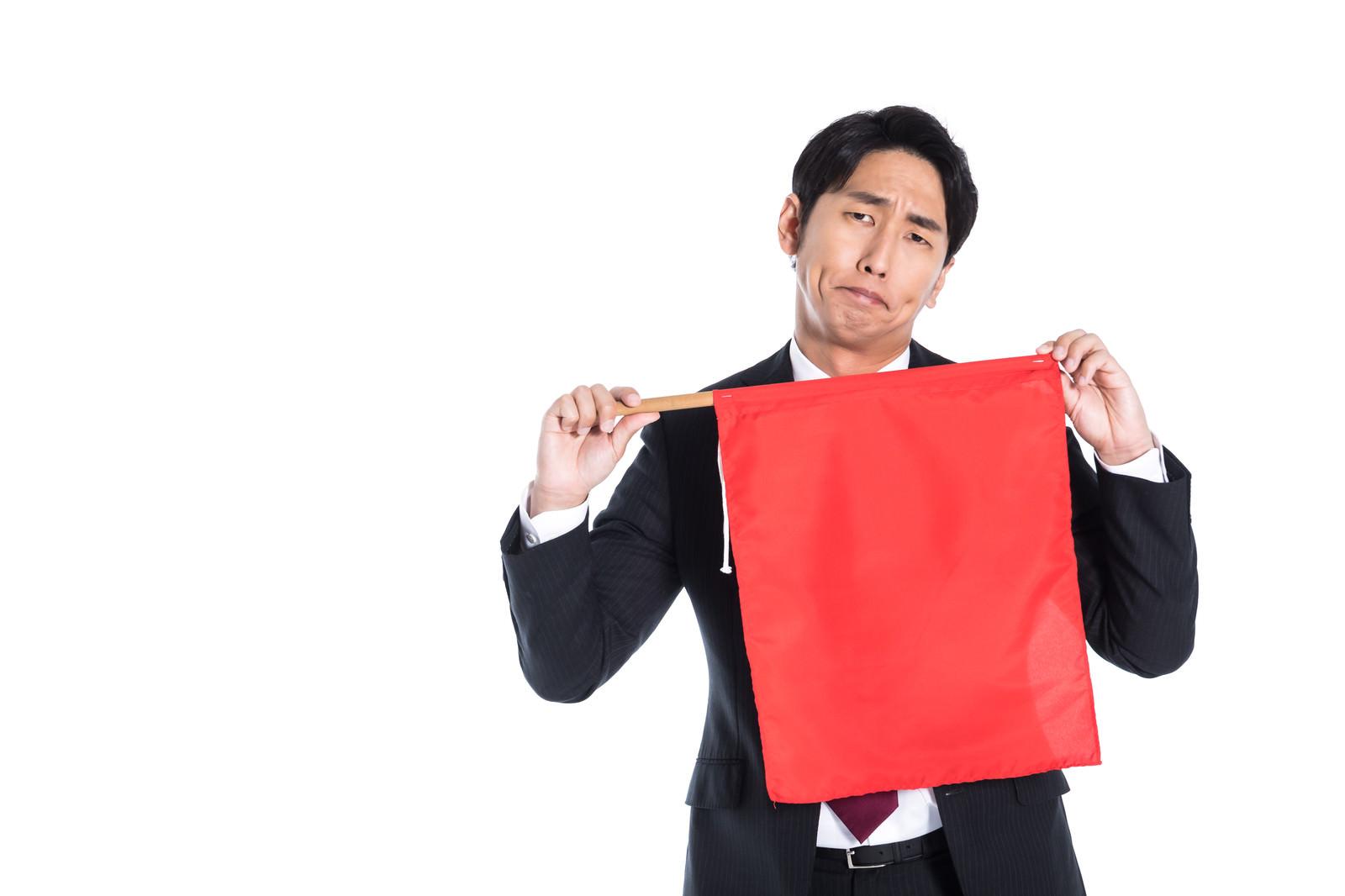 「赤い旗を持って危険を知らせる会社員」の写真[モデル:大川竜弥]