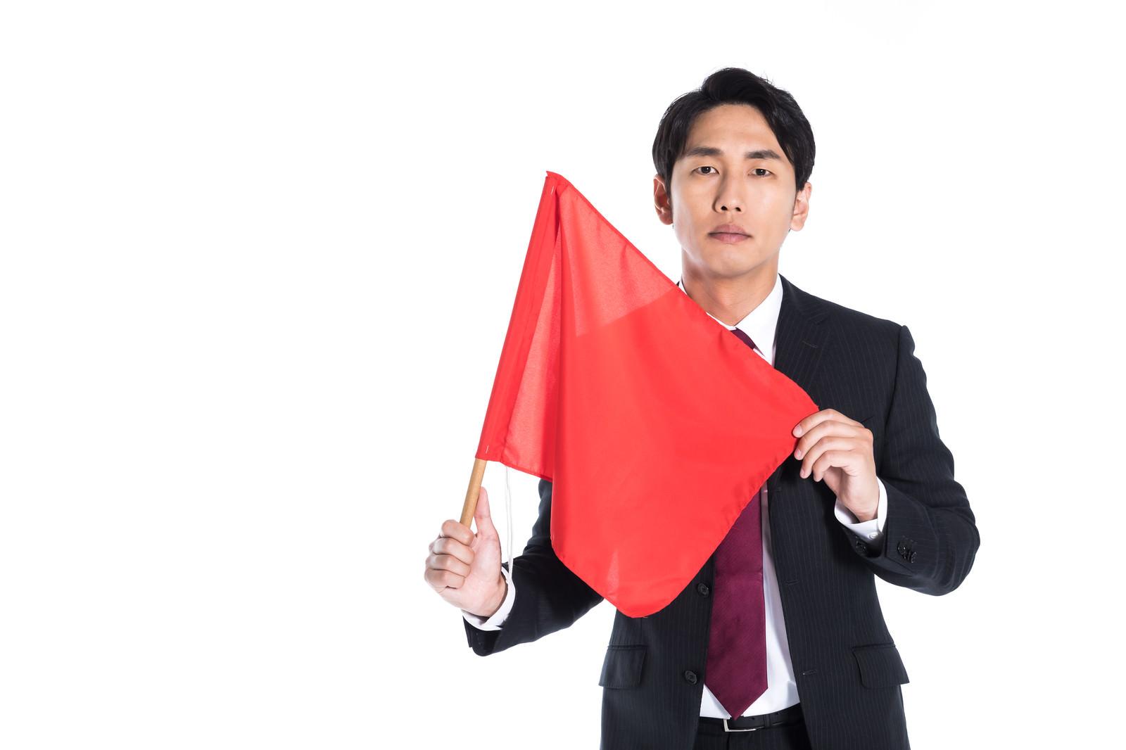 「赤い手旗をもち危険を知らせる会社員」の写真[モデル:大川竜弥]