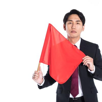 赤い手旗をもち危険を知らせる会社員の写真